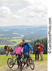 Posando pareja ciclista en la montaña con bicicletas
