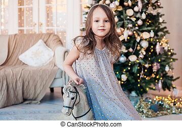 posar, cómodo, contra, niña bonita, árbol., interior, antigüedad, navidad, poco, caballo, mecedor