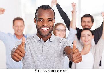 posición, uso, el suyo, grupo, empresarios, arriba, actuación, joven, usted, team., mientras, pulgares, plano de fondo, africano, hombre sonriente, casual, feliz