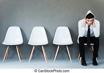 Preocupado por la entrevista. Un joven empresario frustrado cubriendo su cabeza por papel mientras se sienta en la silla contra el fondo gris