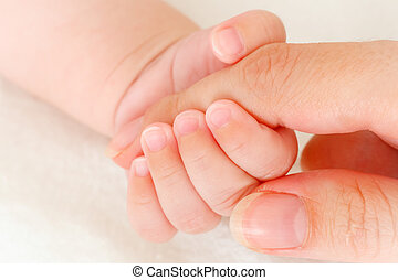 primer plano, tenencia, dedo, la mano de la madre, bebé