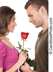 Primera cita. Alegre joven pareja amorosa sosteniendo una rosa roja y sonriendo mientras de pie cara a cara y aislado en el fondo blanco