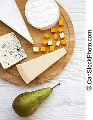 Probando varios tipos de queso con pera sobre fondo blanco de madera. Comida para el vino, buena vista. De plano, desde arriba.