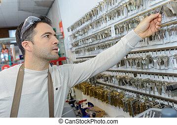 Profesional con diferentes tipos de llaves en el cerrajero