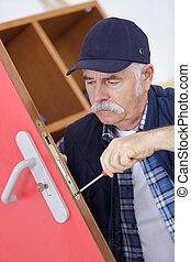 Profesional senior con diferentes tipos de llaves en cerrajero