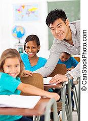 Profesor de escuela primaria ayudando a estudiante