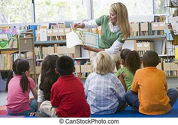 Profesor de guardería leyendo a niños en la biblioteca