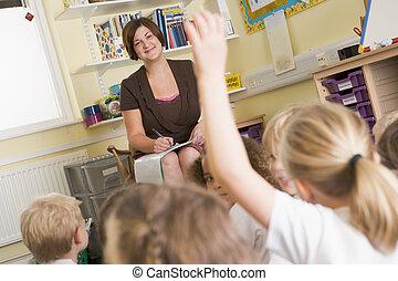 Profesor en clase con estudiantes voluntarios en primer plano (centro selectivo)