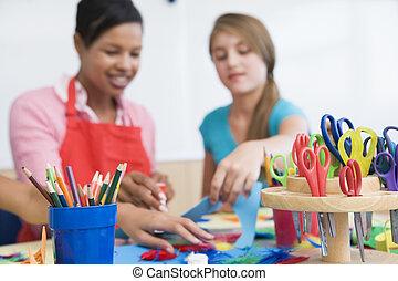 Profesor y estudiante en clase de arte con suministros en primer plano (centro selectivo)