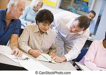 Profesora ayudando a un estudiante maduro en clase
