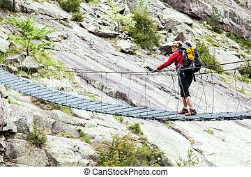 puente cruzando, mochila, mujer, viajando arduamente