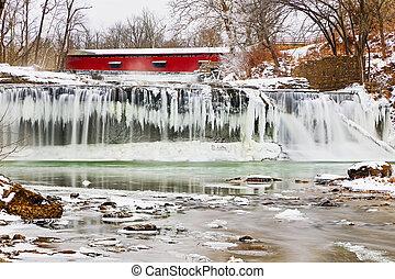 Puente cubierto rojo y cascada congelada