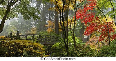 Puente de madera en el jardín japonés en el panorama de otoño
