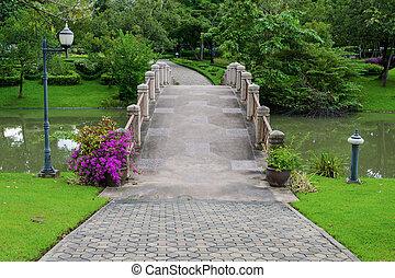 Puentes de cemento y pasillo para hacer ejercicio con árboles en el parque