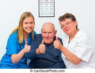 Pulgares arriba de un anciano y sus cuidadores