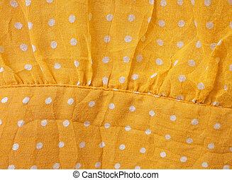 Puntos blancos sobre el fondo de tela amarilla
