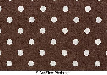 Puntos de polka blanco sobre fondo de tela marrón.
