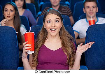 ¡Qué emocionante película! Hermosa joven sosteniendo vasos con soda y gestando mientras se sienta en el cine