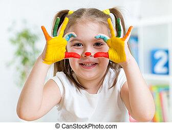 Que la niña se divierta pintando sus manos