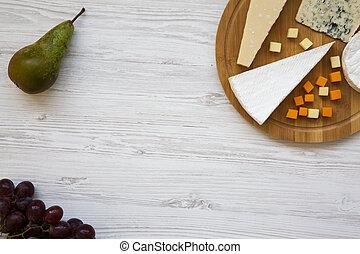 Queso degustador con frutas en fondo blanco de madera. Comida para el vino, buena vista. Copia espacio. Planta. Desde arriba.