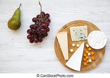 Queso degustador con frutas en fondo blanco de madera. Comida para el vino, buena vista. Espacio para el texto. Planta. Desde arriba.