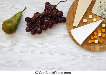 Queso degustador con frutas en fondo blanco de madera. Comida para vino, espacio para copiar. Planta. Desde arriba, desde arriba.