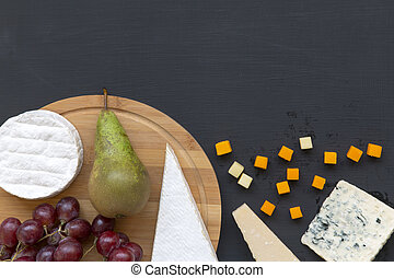 Queso degustador con frutas en fondo oscuro. Comida romántica. Copia espacio. Planta. Desde arriba, desde arriba.
