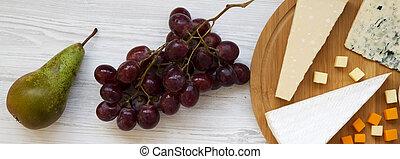 Queso degustador con frutas en mesa de madera blanca. Comida para el vino. Planta. Desde arriba, desde arriba.