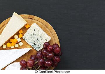 Queso degustador con frutas en tabla de madera en fondo oscuro. Comida romántica. Copia espacio. Planta. Desde arriba, desde arriba.
