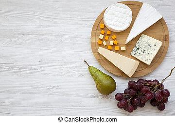 Queso degustador con frutas en un fondo blanco de madera. Comida para el vino, buena vista. De plano, desde arriba. Espacio para el texto.