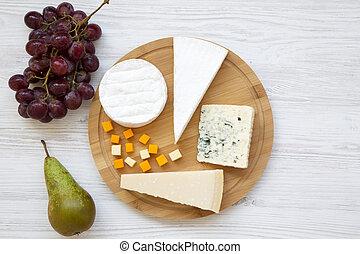 Queso degustador con frutas en un fondo blanco de madera. Comida para el vino, buena vista. Planta. Desde arriba.