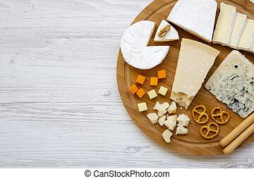 Queso degustador con palitos de pan, nueces y pretzels en el fondo de madera, la vista superior. Comida para el vino. Copia espacio. Desde arriba. Planta.