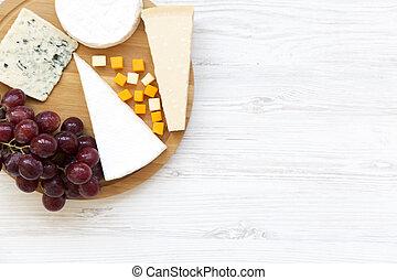 Queso degustador con uvas en fondo blanco de madera. Comida para el vino, buena vista. Espacio para el texto. Planta. Desde arriba.