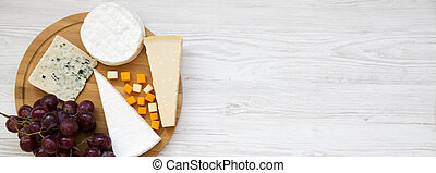 Queso degustador con uvas en una tabla de madera redonda, vista superior. Comida para el vino. De plano, desde arriba. Copia espacio.