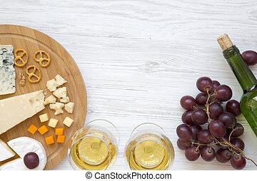 Queso degustador con vino, guirnaldas, nueces y pretzels en el fondo de madera. Comida romántica. Desde arriba. La mejor vista. Planta. Copia espacio.