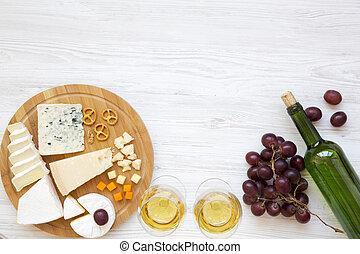 Queso degustador con vino, uvas, nueces y pretzels en el fondo de madera. Comida romántica. Desde arriba. La mejor vista. Planta. Copia espacio.