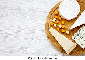 Queso degustador en una tabla de bambú redonda en un fondo blanco de madera. Comida para el vino, buena vista. De plano, desde arriba. Copia espacio.
