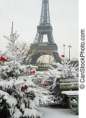 Rara noche nevada en París. La torre de eiffel y el árbol de Navidad decorado