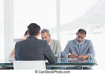 Reclutadores revisando al candidato durante la entrevista de trabajo