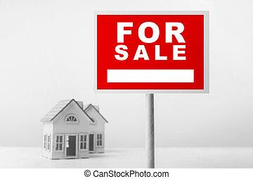 Red para la venta de inmobiliarias delante de una pequeña casa modelo.