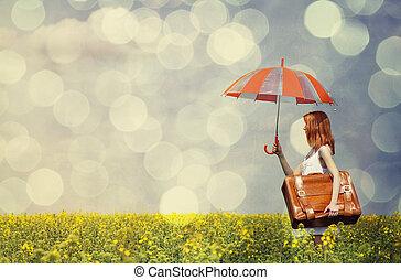 Redhead encanta con paraguas y maleta en el campo de la violación.