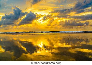 Reflexión de atardecer en la playa