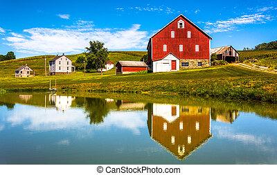 Reflexión de casa y granero en un pequeño estanque, en el condado rural de York, Pennsylvania.
