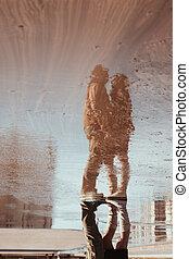 Reflexión en el charco de mujer y hombre abrazados bajo el paraguas durante la lluvia