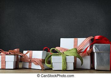 Regalos de Navidad en el escritorio con antecedentes de pizarra