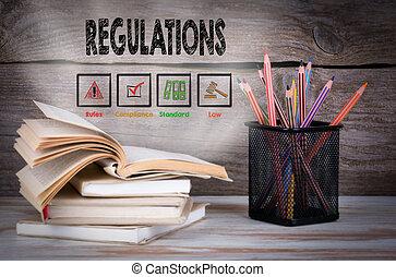Reglamentos. Un montón de libros y lápices en la mesa de madera.