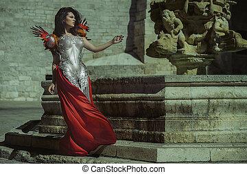 Reina glamorosa con armadura de plata y oro, hermosa mujer morena con abrigo rojo largo y cabello castaño