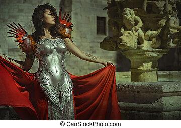 Reina real con armadura de plata y oro, hermosa mujer morena con abrigo rojo largo y cabello castaño