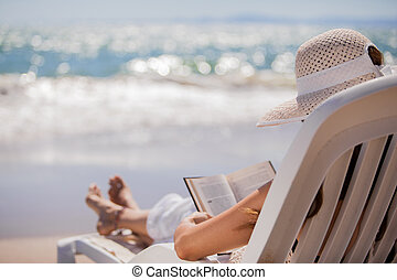 Relajándose y leyendo en la playa
