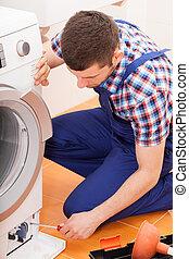Reparador arreglando lavadora